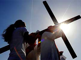 a large cross is transferred from one person to another during the Stations of the Cross in Reparation for Abortion on Good Friday 201  in Rochester, N.Y. CNS photo/Mike rupi, Catholic Courier