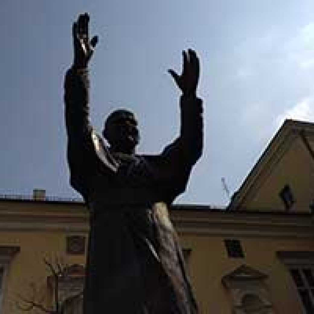 A statue of St. John Paul II with his arms raised in a greeting welcomes visitors to Krakow, Poland.