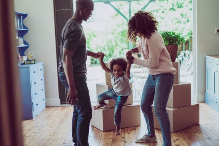 : A family—mother, father, and little girl—plays together whlie unpacking boxes in their home